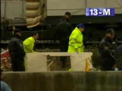 Unos operarios rodeados de policías pasan ante el coche 5 llevando una pieza que bien pudiera ser la que se ve arriba a la izquierda en la foto anterior