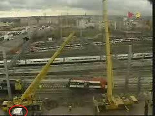 La mitad delantera del coche 4 suspendida de las grúas. A la izquierda, la locomotora que colabora en el movimiento del tren