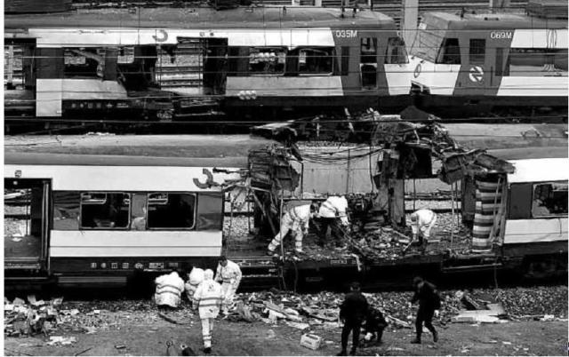 Agentes policiales buscan entre los restos, mientras los cochas 3 y 4 del tren de Atocha pasan por detrás. Son aproximadamente las 13 h