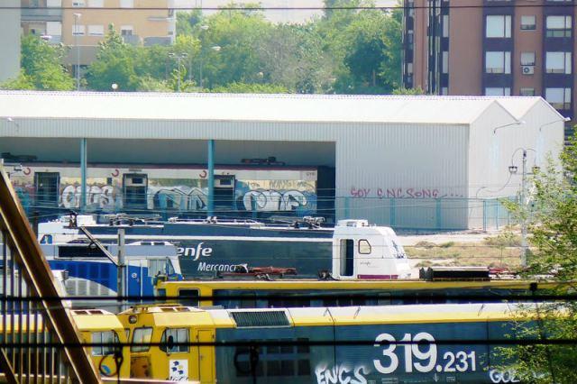 7 de mayo de 2009. Material ferroviario estacionado en el taller TCR de Villaverde. Al fondo una nave con su fondo cerrado alberga un coche de cercanías