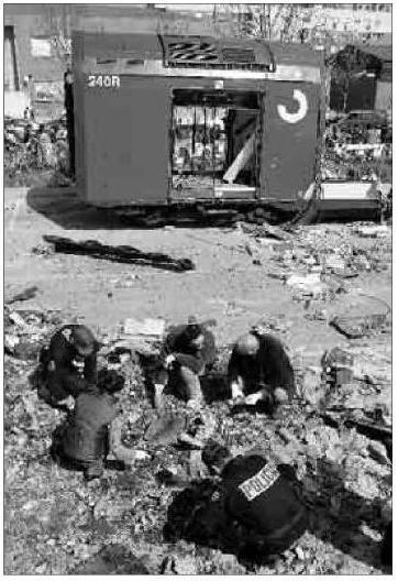Foto de El Mundo del 16 de marzo de 2004. Policías buscando, el 15 de marzo de 2004, entre los restos del coche 5 de El Pozo