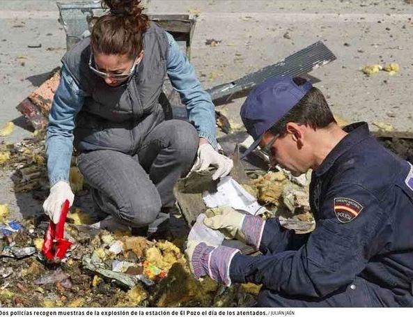 """Foto de El Mundo del 9 de marzo de 2011 (pie de foto erróneo, no está tomada """"el día de los atentados"""", sino cuatro días después)). Policías buscando, el 15 de marzo de 2004, entre los restos del coche 5 de El Pozo"""